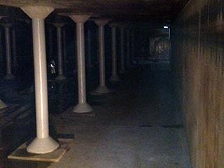 dark room with light shining on white pillars