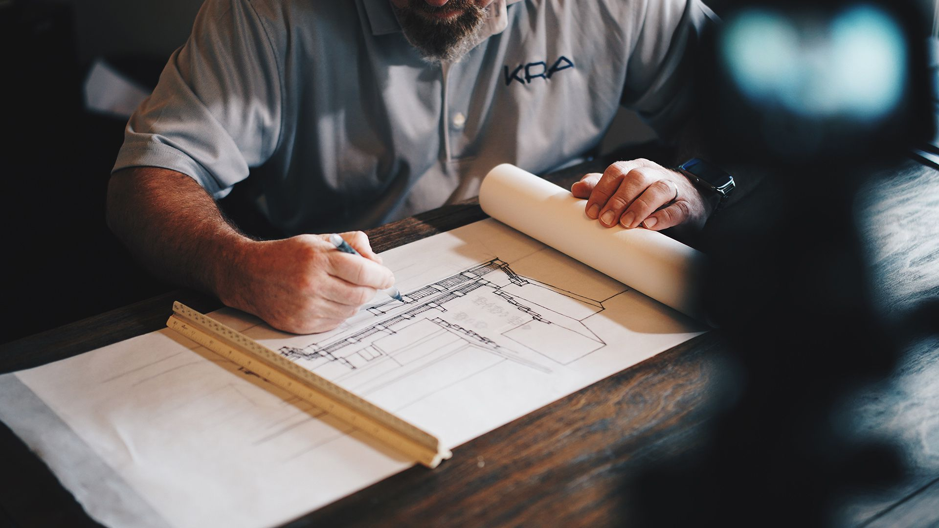 man with beard drawing blueprints on a wood table