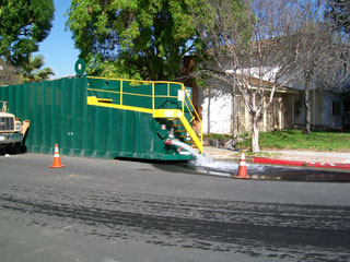 green dumpster and yellow ladder attached with water pouring out onto the street